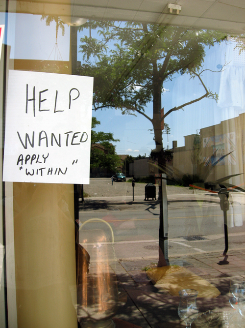 A help wanted sign on a restaurant window. It reads: