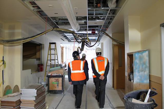 Construction workers touring a building with their hard hats on