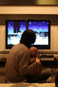 Father with baby watching tv