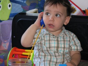 A toddler answering a pretend phone