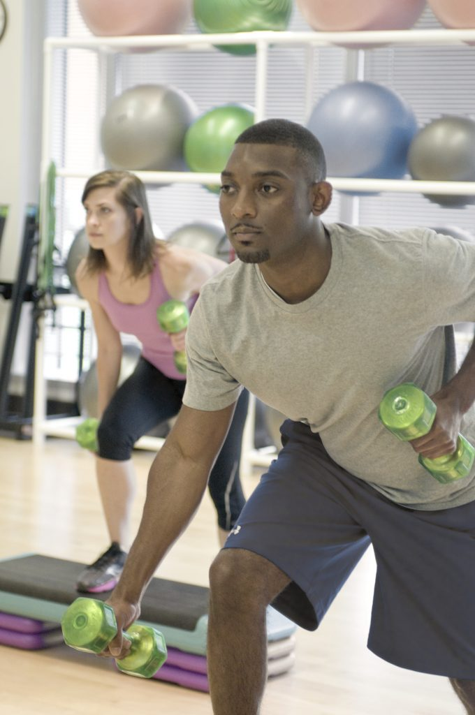 Two people with weights doing aerobic exercise.
