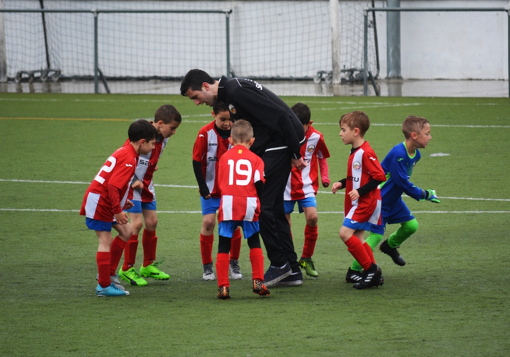 Children on a soccer field with their coach