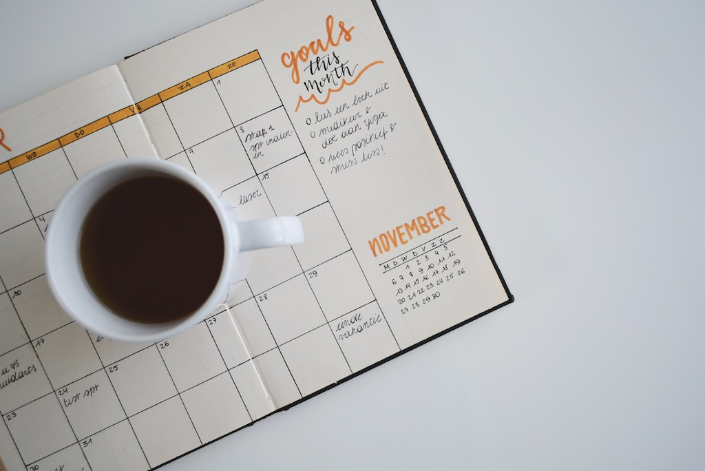 A photo of a coffee cup sitting on a calendar.  The calendar has a section for goals this month.
