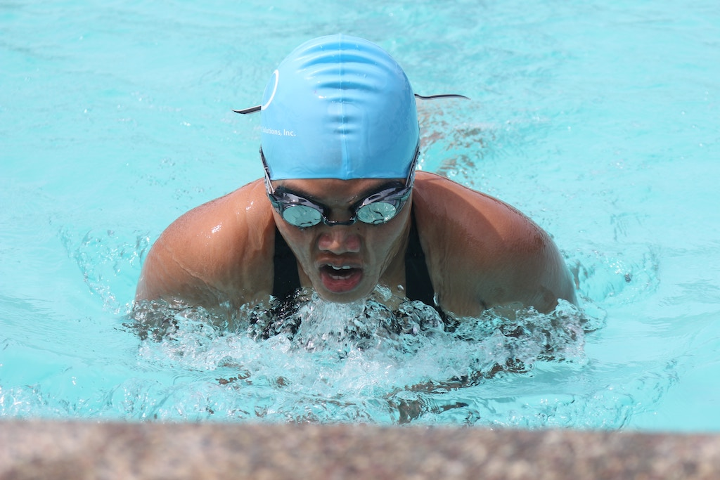 A person swimming in a pool with goggles and swimcap.