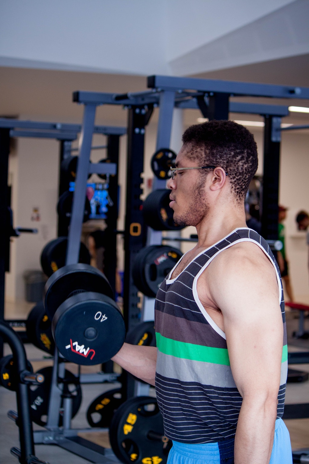 A man lifting a 40 pound dumbbell in a gym setting.