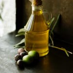 Picture of a small bottle of olive oil with black and green olives laying at the base.