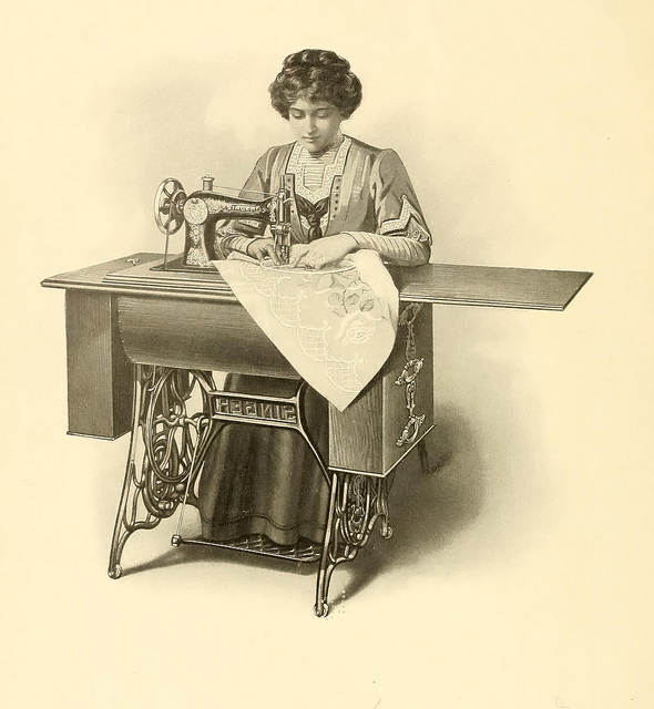A woman sewing using an old foot-pedal sewing machine
