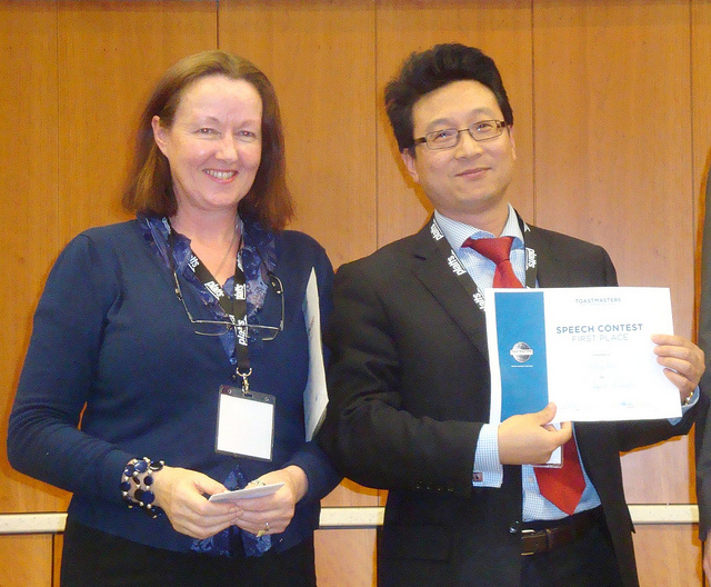 A woman and a man smiling as he holds a certificate for having won an Evaluation Contest