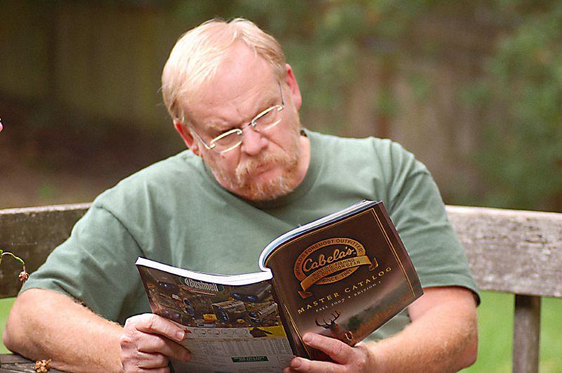 An outdoorsman reading a Cabela's' catalog