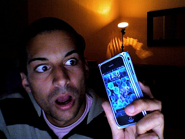 Man with a surprised face looking at his iPhone