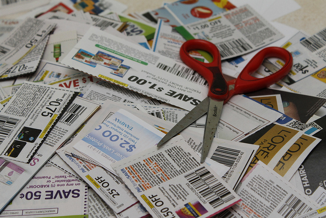 A large pile of coupons on a table with a scissors resting on top