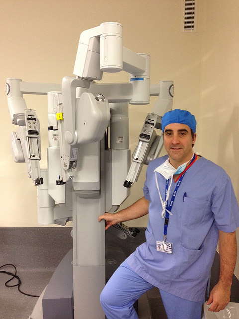 A surgeon standing next to the da Vinci robot