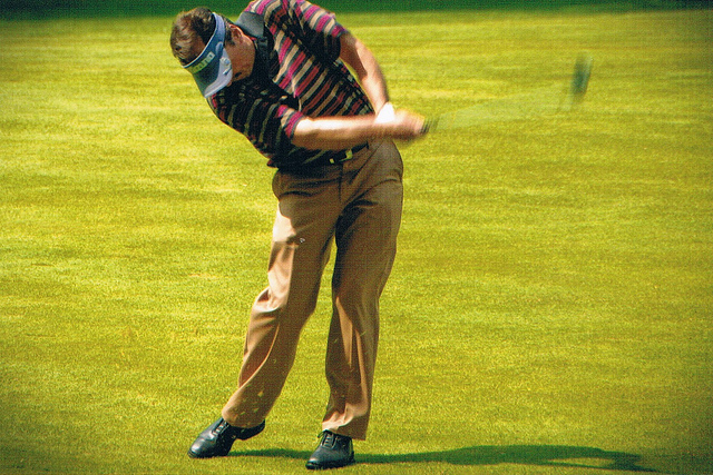 a man mid-swing playing golf