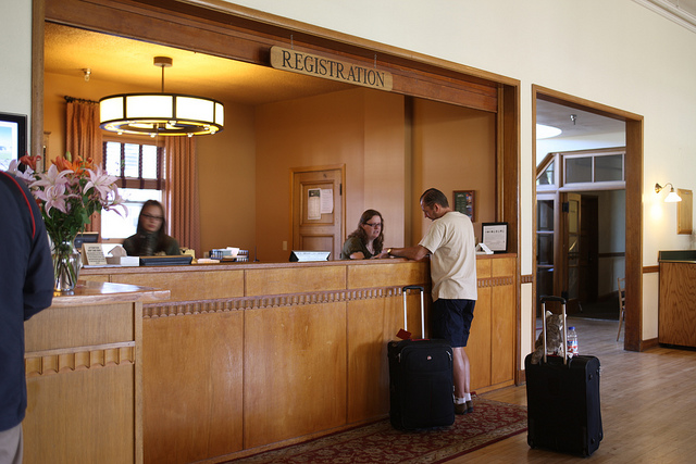 A man checking out of the Mammoth Hot Springs Hotel registration desk in Yellowstone National Park