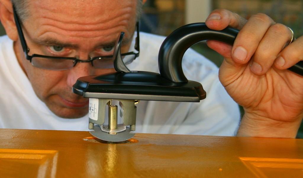 A handyman, up close, fixing a door