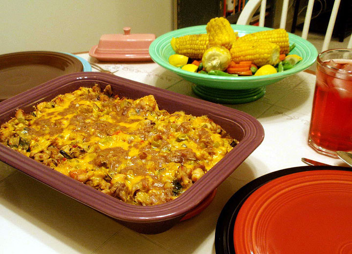 King Ranch Chicken casserole  on a table with a bowl of mixed vegetables. All very tasty looking.