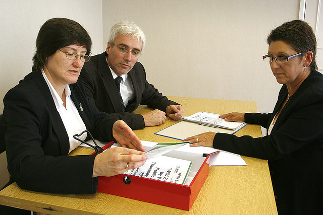 Two people interviewing a woman