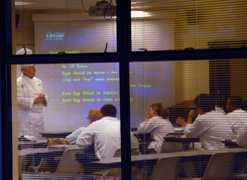A chef teaching his class how to make Caviar, using the help of a powerpoint