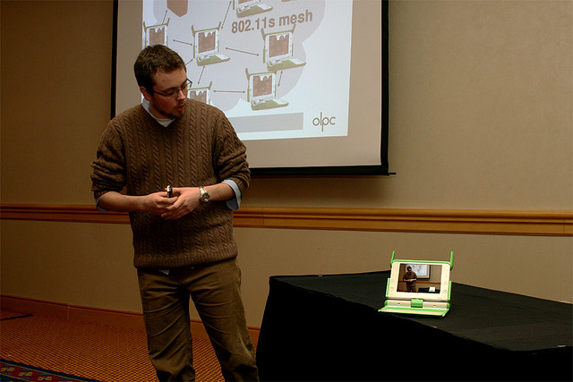 A man presenting on a small tablet